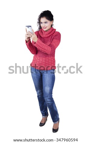 Full length of beautiful indian woman standing in the studio while wearing winter clothes and typing message on smartphone - stock photo