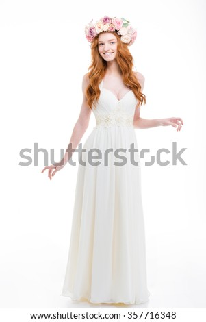 Full length of beautiful smiling young bride with long red hair in white dress and wreath of pink roses standing over white background - stock photo