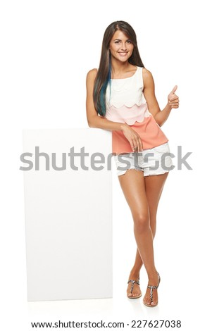 Full length of beautiful tanned woman in shorts standing leaning on white blank advertising board banner and showing approving sign, over white background - stock photo