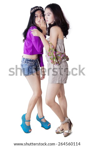 Full length of beautiful teenage girls standing in the studio while gossiping and bullying someone - stock photo