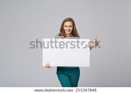 Full length of beautiful woman standing behind, holding white blank advertising board banner, on gray background