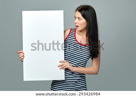 Full length of beautiful woman standing behind, holding white blank advertising board banner, on gray background - stock photo