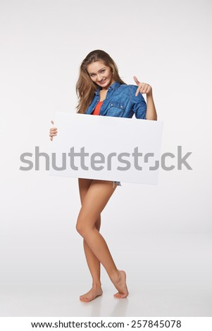 Full length of beautiful woman standing behind, holding white blank advertising board banner, over white background  - stock photo
