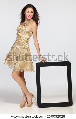 Full length of beautiful woman wearing golden cocktail dress standing leaning on frame with blank copy space for advertising, over gray background - stock photo