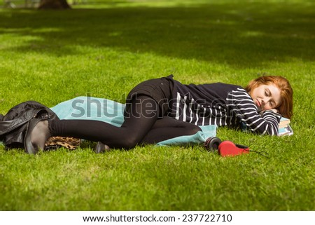 Full length of beautiful young woman lying on grass at the park - stock photo