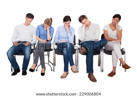 Full length of bored businesspeople sitting on chairs against white background - stock photo