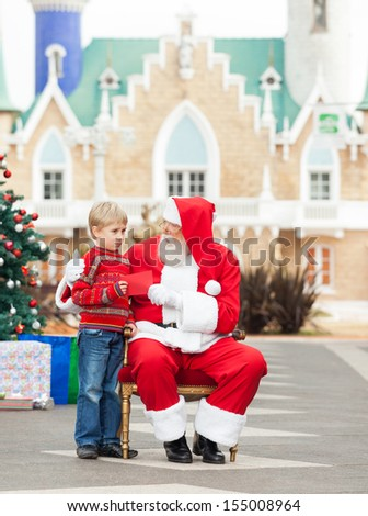 Full length of boy giving letter to Santa Claus against house - stock photo