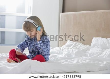 Full length of boy listening music on headphones in bedroom - stock photo