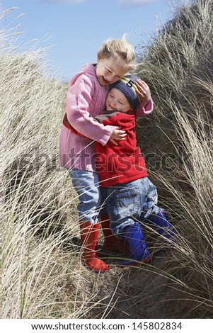Full length of brother and sister embracing in long grass - stock photo
