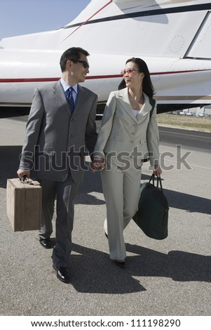 Full length of business couple walking together with luggage at airport - stock photo