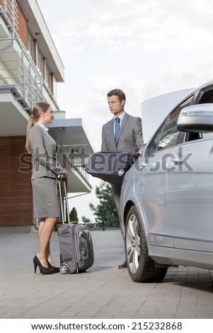 Full-length of business couple with luggage outside hotel - stock photo