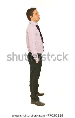 Full length of business man standing in profile with hands in pockets pants and looking away isolated onw hite background - stock photo