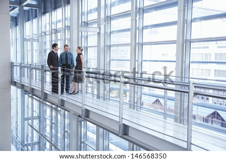 Full length of business people discussing by railing in modern office - stock photo