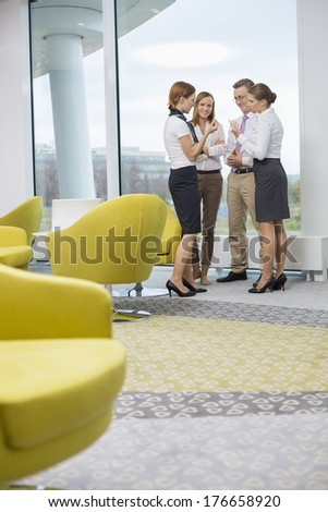 Full length of business people discussing in lobby - stock photo