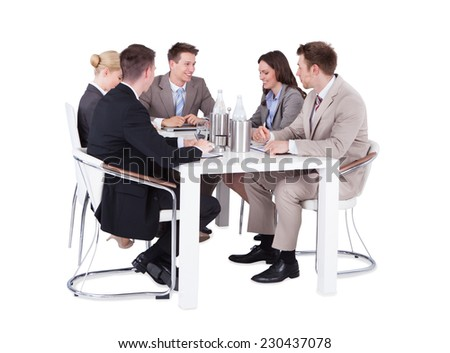 Full length of business people having conference meeting over white background - stock photo