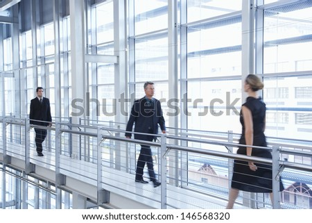 Full length of business people walking by railing in modern office - stock photo