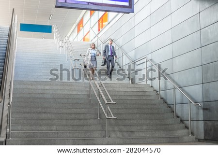 Full length of businessman and businesswoman walk down stairs at railway station - stock photo