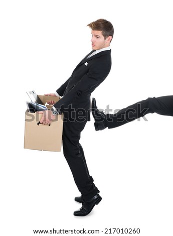Full length of businessman carrying cardboard box with leg kicking him against white background - stock photo