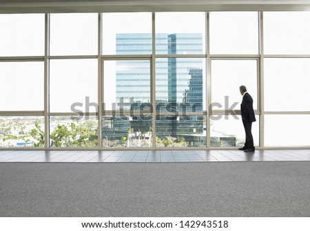 Full length of businessman looking out of office window - stock photo