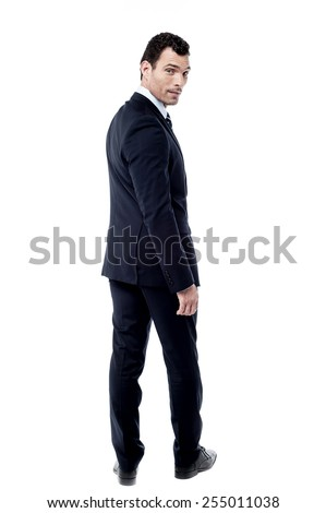 Full length of businessman looking over his shoulder - stock photo