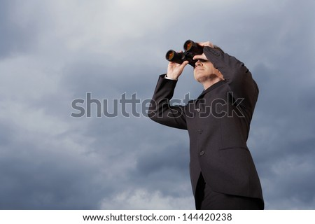 Full length of businessman looking through binoculars against cloudy sky - stock photo