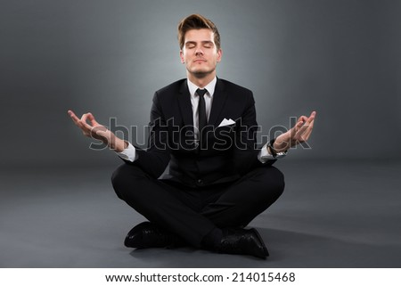 Full length of businessman practicing yoga in lotus position over gray background - stock photo