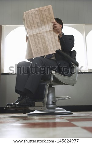Full length of businessman reading newspaper while waiting for haircut in hair salon