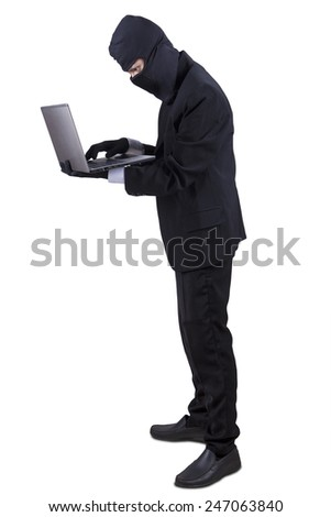 Full length of businessman wearing black mask, stealing information on laptop computer