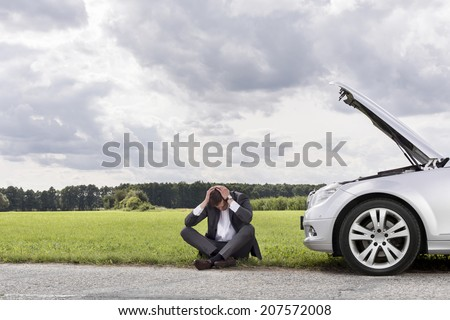 Full length of businessman with hands on head sitting by broken down car at countryside - stock photo