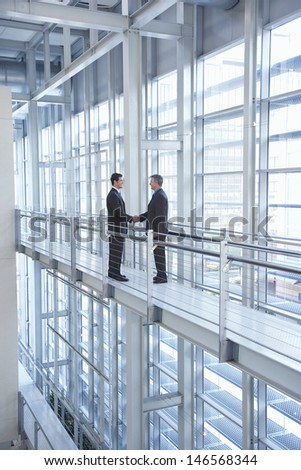 Full length of businessmen shaking hands by railing in modern office - stock photo
