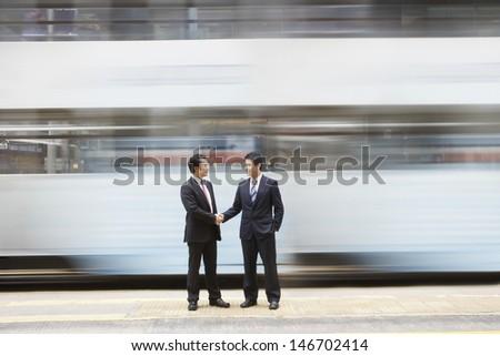 Full length of businessmen shaking hands on busy street - stock photo