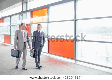 Full length of businessmen with briefcase walking in railroad station - stock photo