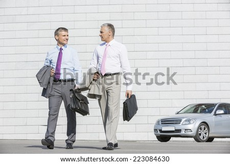 Full length of businessmen with briefcases walking on street - stock photo