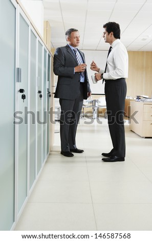 Full length of businessmen with coffee cups discussing in office corridor - stock photo