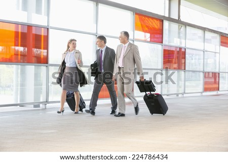 Full length of businesspeople with luggage walking on railroad platform - stock photo