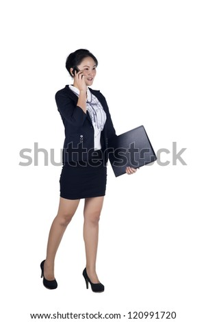 Full length of businesswoman walking talking on mobile phone and holding folder, isolated on white background. Model is Asian woman. - stock photo