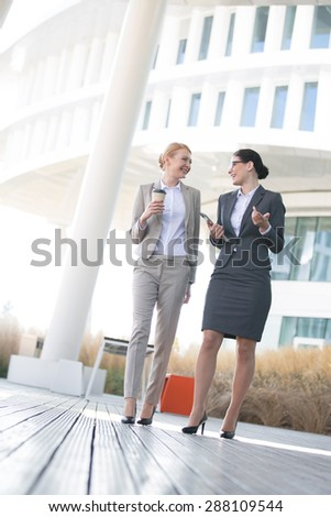 Full-length of businesswomen conversing outside office building - stock photo