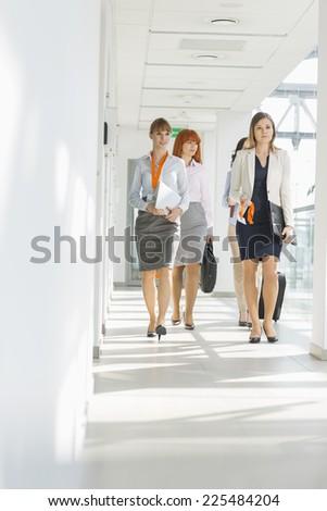 Full-length of businesswomen walking at office hallway - stock photo