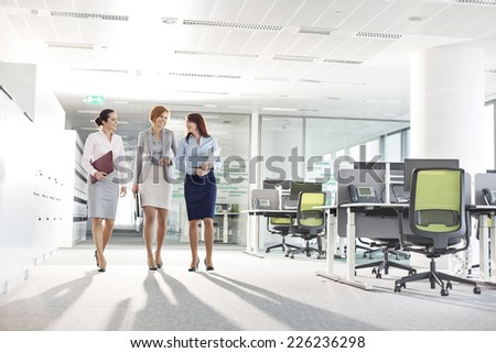 Full-length of businesswomen with file folders walking in office - stock photo