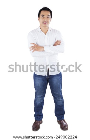 Full length of casual man standing in studio while smiling at the camera, isolated on white background - stock photo
