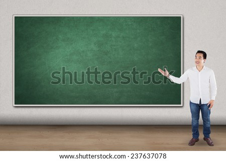 Full length of casual man standing in the class and showing blank chalkboard - stock photo