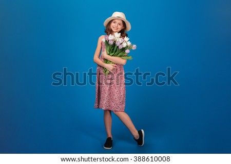 Full length of charming cheerful little girl standing and holding bouquet of flowers over blue background - stock photo