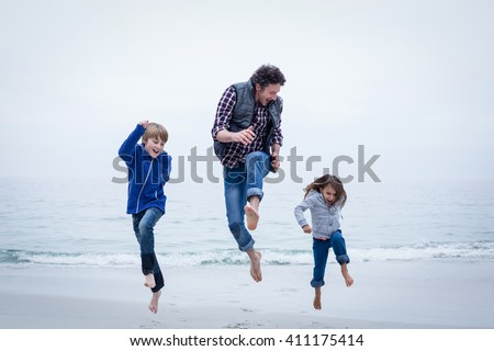 Full length of cheerful family jumping at sea shore against clear sky - stock photo