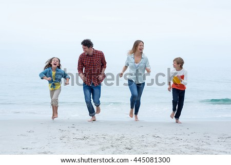 Full length of cheerful family running at sea shore against sky - stock photo