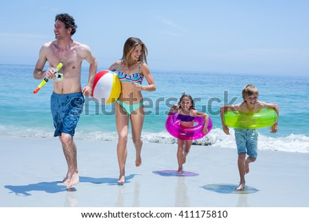 Full length of cheerful family running with swimming equipment at sea shore - stock photo