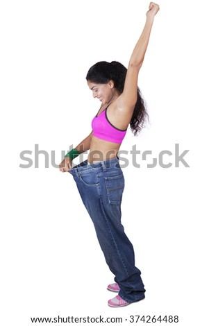 Full length of cheerful indian woman wearing old jeans and feeling success to weight loss - stock photo