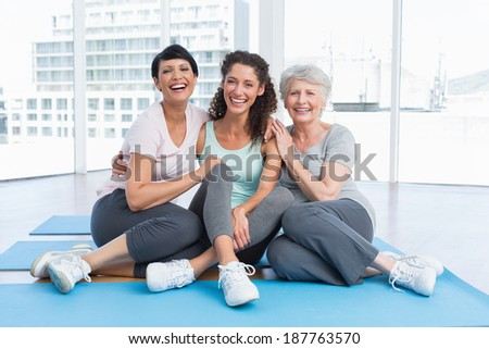 Full length of cheerful women sitting in the yoga class - stock photo
