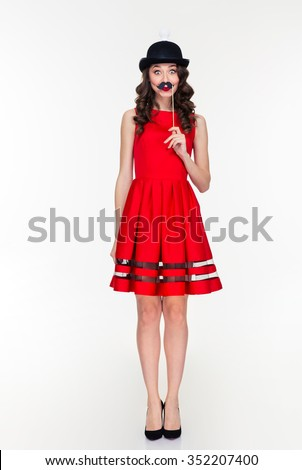 Full length of comical amusing young woman in red dress and ridiculous black hat with light bulb holding fake moustache on stick - stock photo