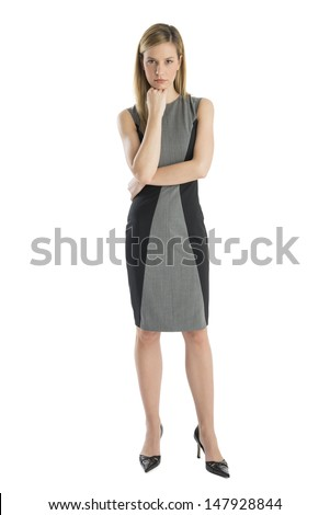 Full length of confident businesswoman with hand on chin standing against white background - stock photo