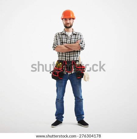 full length of confident workman with tools in orange helmet standing over light background - stock photo